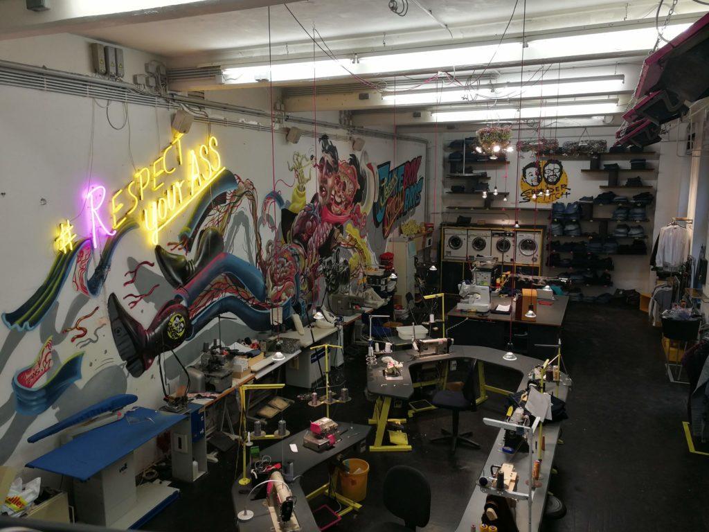 Werkstätte Gebrüder Stitch Jeans - Nähmaschinen, Waschmaschinen, Murals auf der Wand.