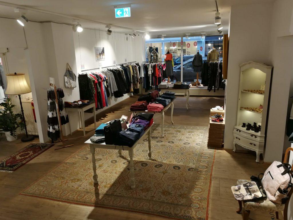 Nachhaltiger Shop bei der Mariahilferstrasse - im Erdgeschoss - auf Tischen Pullover, Taschen, hängend Mäntel und Jacken.